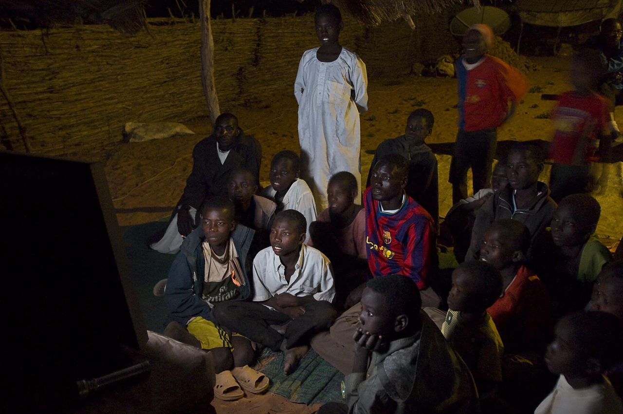 In Djabal, refugees watch TV in a television playground create and run by the three Umda (traditionnal leaders) on the camp. In the evening, people come to watch programs: sports, songs, movies, news... There are 5 televisions set to offer a choice as wide as possible. On the first screen, news are displayed (bbc, aljazzera, télétchad, sudanese TV), on the second actions movies, cartoons, on the third songs, entertainment from Sudan, Nigeria, Eritrea,... on the fourth sports, and on the last one football only. People pay 50 CFA (0.11 USD) for the whole evening. The project is run like an association. The money pays for diesel, engine maintenance... There are approximately 15 places to pay and watch TV in the camp, « but they ask 100 CFA (0.22 USD) », says an Umda. Created on 4 june 2004, Djabal camp sheltered 17.766 persons and 4.681 families in december 2011. It is located 4 kilometers west from Goz Beida, 217 kilometers south from Abeche, 900 kilometers east from N'Djamena the capital and 80 kilometers from the sudanese border.