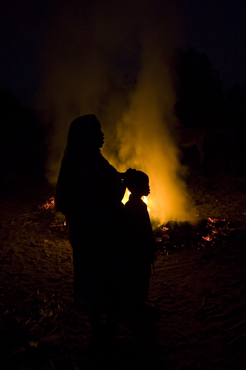 In a street of the Djabal camp, a woman and her son watch an heap of garbages burning. All day long, refugees get rid of their waste in a hole. When evening comes, a refugee trained by an ngo, set fire to it and wathc over to avoid any propagation of fire. Created on 4 june 2004, Djabal camp sheltered 17.766 persons and 4.681 families in december 2011. It is located 4 kilometers west from Goz Beida, 217 kilometers south from Abeche, 900 kilometers east from N'Djamena the capital and 80 kilometers from the sudanese border.