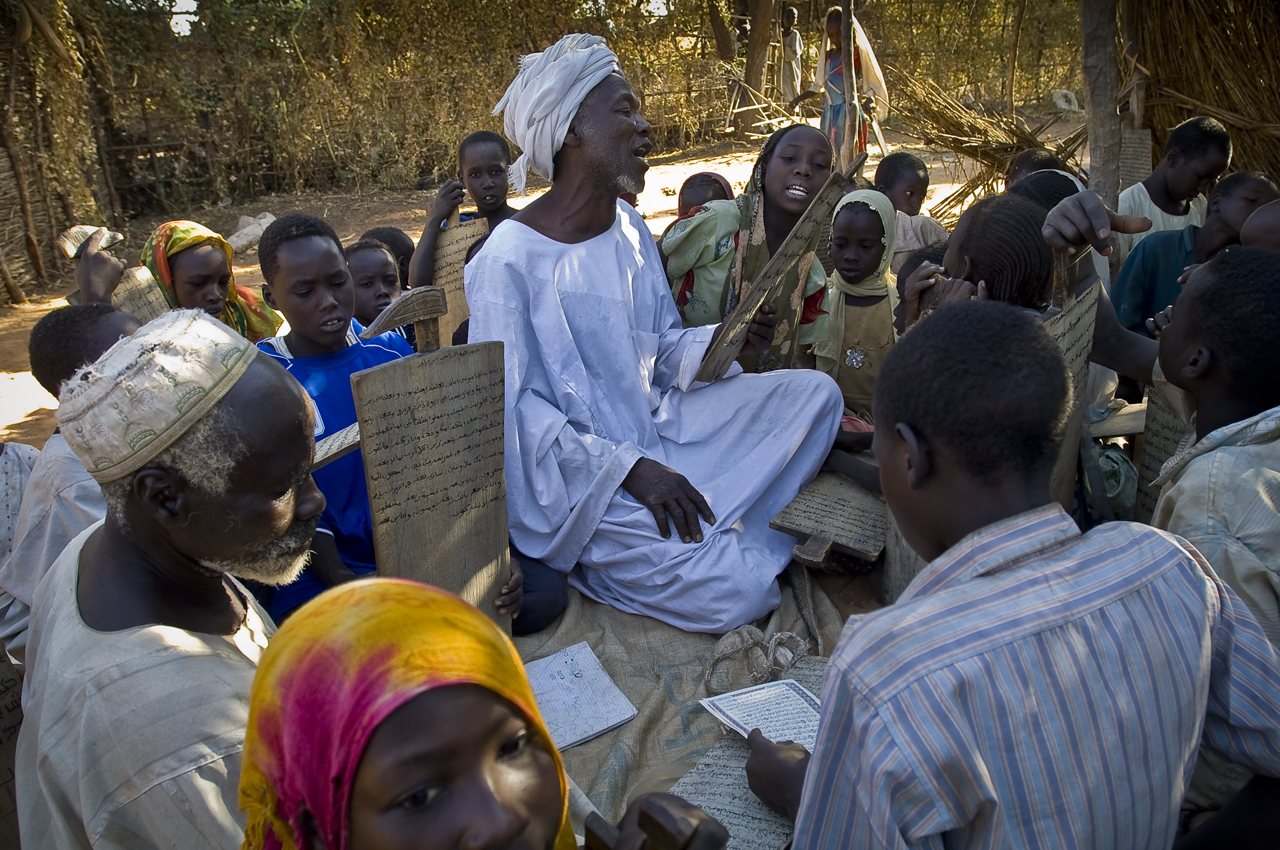 """In Nour Al Islam coranic school, one of the madrassa of Djabal refugees' camp, the marabout, Juma Ibrahim Abdallah, chants verses that he reads from the small wooden board (alluha) where pupils write down sura, using black ink and a wooden pen (calam). 88 children from the area attend the madrassa, in mixed session (boys and girls). For Juma Ibrahim Abdallah: """"These children are like my own children.""""  Created on 4 june 2004, Djabal camp sheltered 17.766 persons and 4.681 families in december 2011. It is located 4 kilometers west from Goz Beida, 217 kilometers south from Abeche, 900 kilometers east from N'Djamena the capital and 80 kilometers from the sudanese border."""
