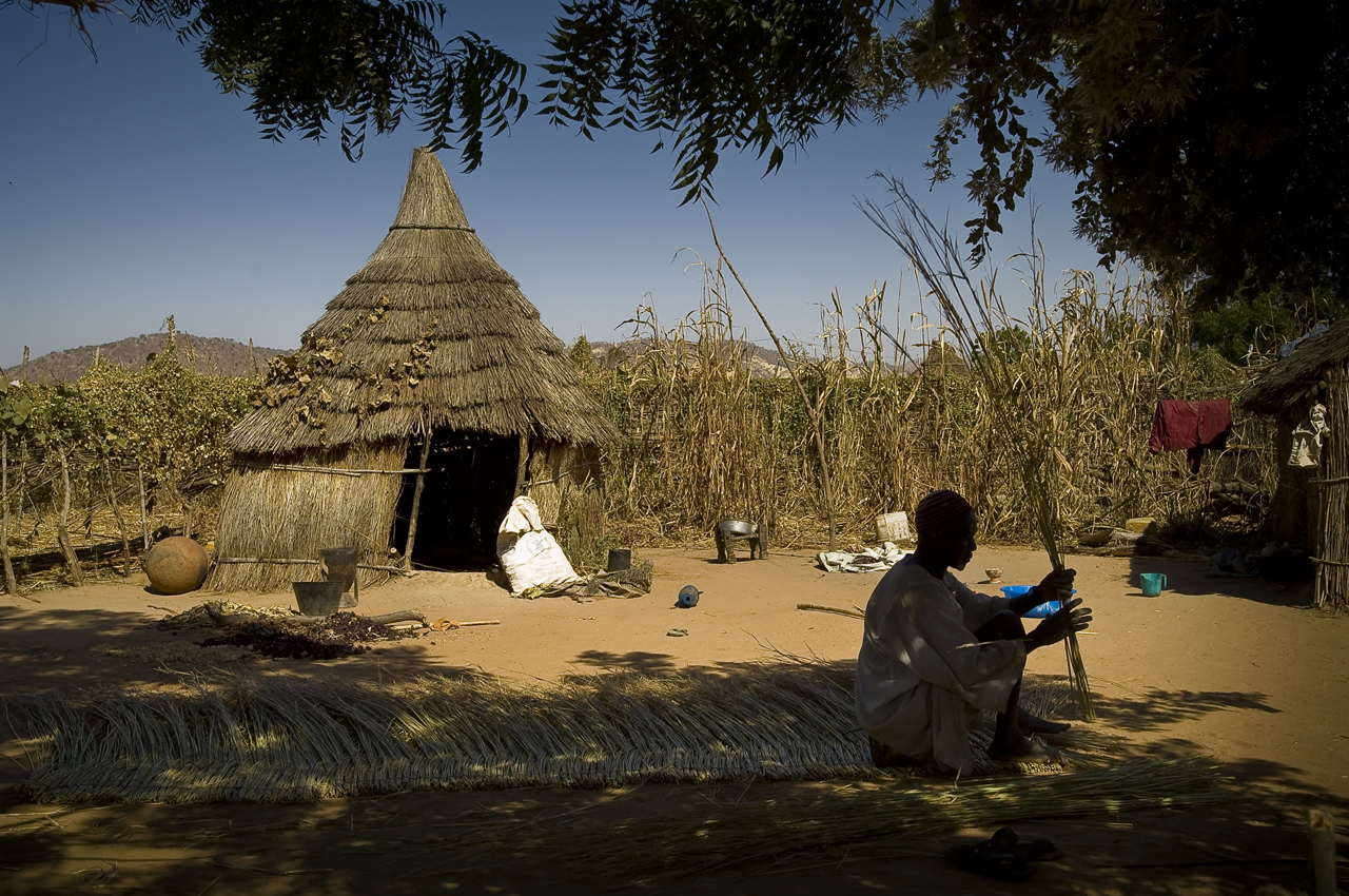 """Sitting under the shade of a tree, in his compound, a refugee makes straw panel used for roof. He sell it for 2000 CFA (4.18 USD). """"Two days are necessary to make a panel. One day to collect the straw out of the bush and one day to make it."""" Looking for cash money, the refugies do income activities.  Created on 4 june 2004, Djabal camp sheltered 17.766 persons and 4.681 families in december 2011. It is located 4 kilometers west from Goz Beida, 217 kilometers south from Abeche, 900 kilometers east from N'Djamena the capital and 80 kilometers from the sudanese border."""
