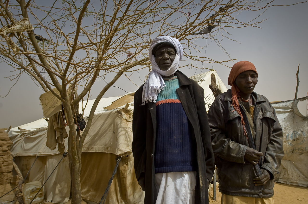 """A couple in the courtyard of their home. Saleh Hamid Abdul 80 years old and his wife, Foko Abakar Ahmed 35. No house but a tent. The woman: """"We arrive 7 years ago, my husband, five children and I. Then we got another child in Chad. We came from Fasher. Seven days to reach Chad."""" The husband comes. In a sigh, he tells his wife: """"Tell them that everything is ok for us, don't say anything bad about the camp. Everything is ok except the tent. It's getting old."""" Afraid to be forcibly brought back to Darfur, the old man warns his wife not to complain, but to describe Oure Cassoni as an haven.... He resumes: """"I am a keeper in the food distribution center and get 25 000 CFA (53 $) a month thanks to Acted (an ngo). Two of my children (16 and 17 years old) study in Sudan because there is no E-level in Oure Cassoni. The oldest is in Khartoum. He lives like a displaced person... I got some news from my fields, in Darfur. No one is cultivating them. Houses of the village have been bombed but some are still standing. My house has been burnt. Only God knows my future."""" Oure Cassoni camp (31 800 refugees in december 2011), 18 kilometers north from Bahai, 361 kilometers north-east from Abeche, 17 kilometers from the sudanese border, was opened in july 2004."""