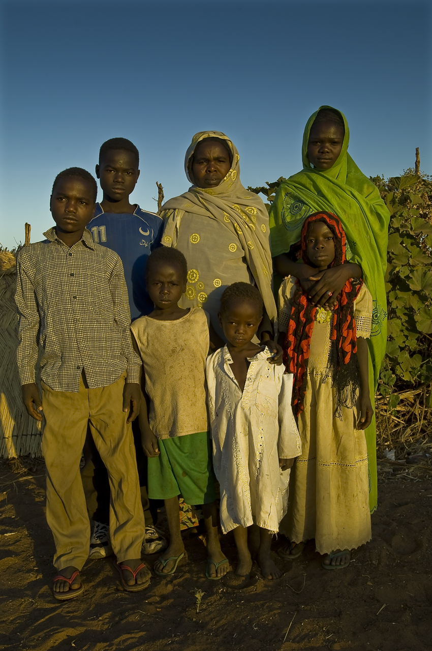 """Mariam Issac Hassan poses with her six children in the compound of her home. Safia Ahbab Abdulaye, 16 years old (girl on the right), Nusur Ahbab Abdulaye, 14 years old (boy in blue tee-shirt), Tahir Ahmat Ali, 12 years old (left with shirt), Gisima Abdulaye Yacoub, 9 years old (girl with red scarf), Khatir Abdulaye Yacoub, 6 years old (with green shorts) and Said Abdulaye Yacoub, 4 years old (boy with white tunic). Mariam arrived in Djabal in 2004. """"I left Sudan with 5 children. I gave birth in Chad to the last one, Said. I was living in Tukul in Dafur, close to Bayda."""" She was supposed to be relocated in a different country as she is disabled and cannot walk easily. """"I was ready to go anywhere to get treatment, no matter no country. I would have left with my children. I was sent to Abeche (221 kilometers from Djabal) where I spent two years in the transit center. Nothing happened. I was taken back to the camp, five months ago. I don't know why I could not leave. No explanations. The problem seems to be the form that the father have to sign to let the children go. My children are from different fathers. One did not want to sign the form. he finally accepted. But then rose other problems that I don't understand... So here I am, in Djabal."""" She waited two years in vain in Abeche. """"I have no choice except accepting the situation. This is not my country, I am seeking help for treatment in a country which is not mine. I cannot do anything to push my destiny. May be God does not want me to travel."""" Being disabled, she cannot work in a field. """"My children found a field and worked on it, but it did not give us anything. Lack of water and rain. We rely on food distributions. I do not know what future can be like. I am disabled and sick. I do not have future any more. I only hope for my children. If they could study. I never live a nice period in my life. I lost my father before I am born. My mother raised me. I marry the father of my first two children. We were arguing all t"""