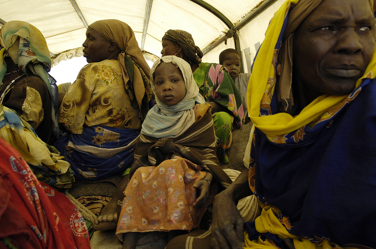 Sitting in a truck, refugees waiting to be moved from Birak, a Chadian village, to camp, 4 hours drive from there.