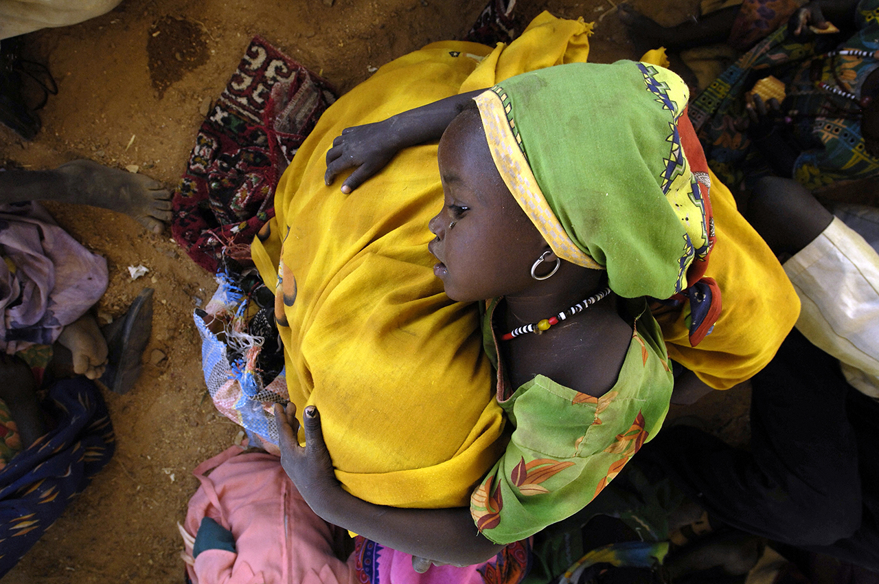 After the truck trip from Birak, upon her arrival in Kounoungo, an exhausted little girl leaning on her mother.