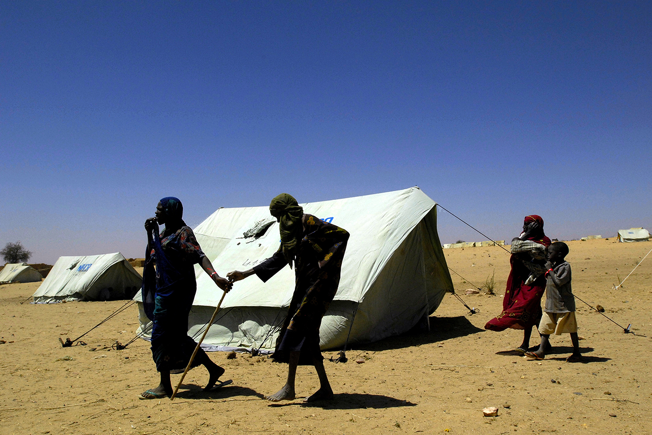 An old and blind refugee being pulled by a relative between the tents in Kounoungo camp.