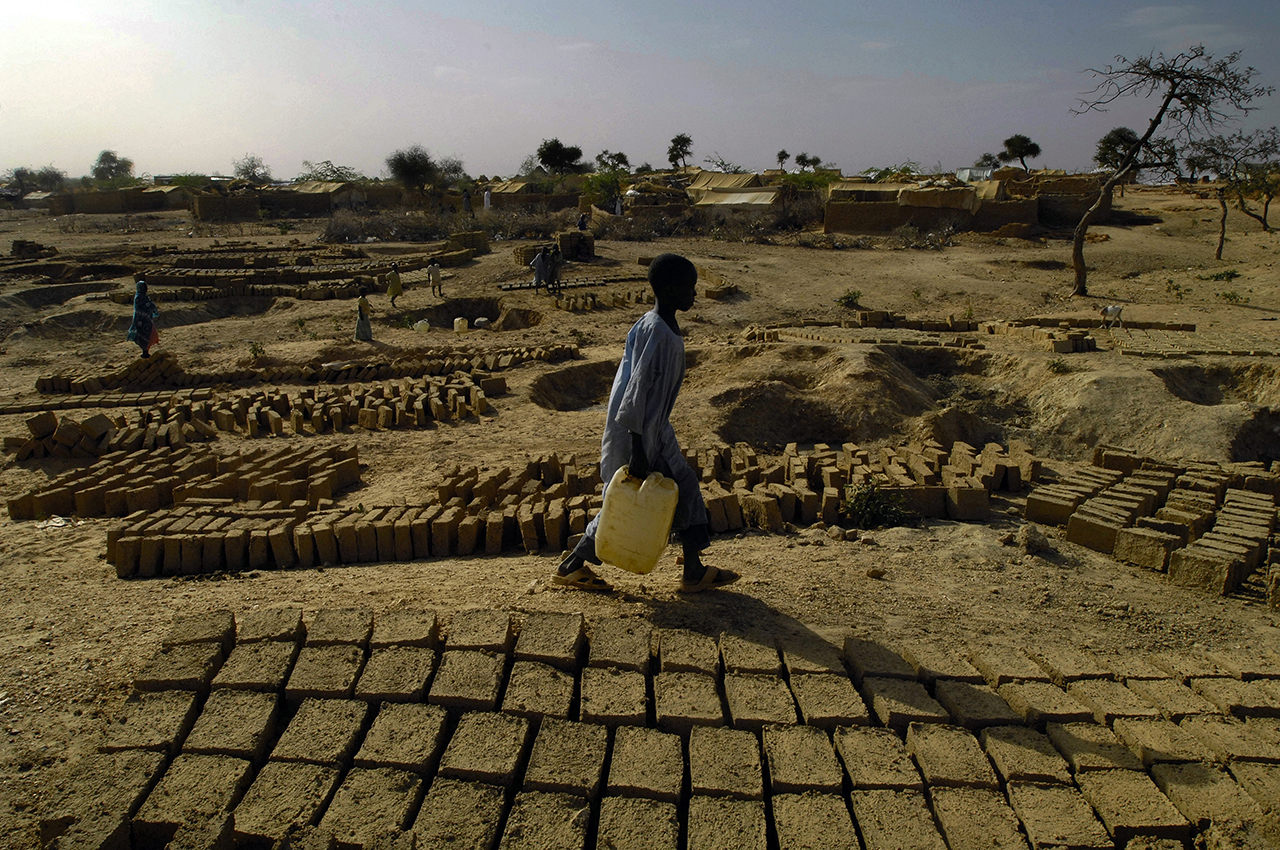 Kounoungo. Refugee brings water to make bricks. This raises issue of water supply because refugees use treated water meant for human consumption.