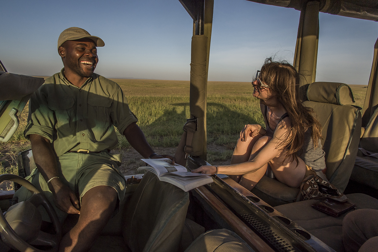 A young American bride jokes with a guide, in the 4x4 which brings them in late afternoon tour. She chose, along with her husband, the Serengeti, as a honeymoon destination.