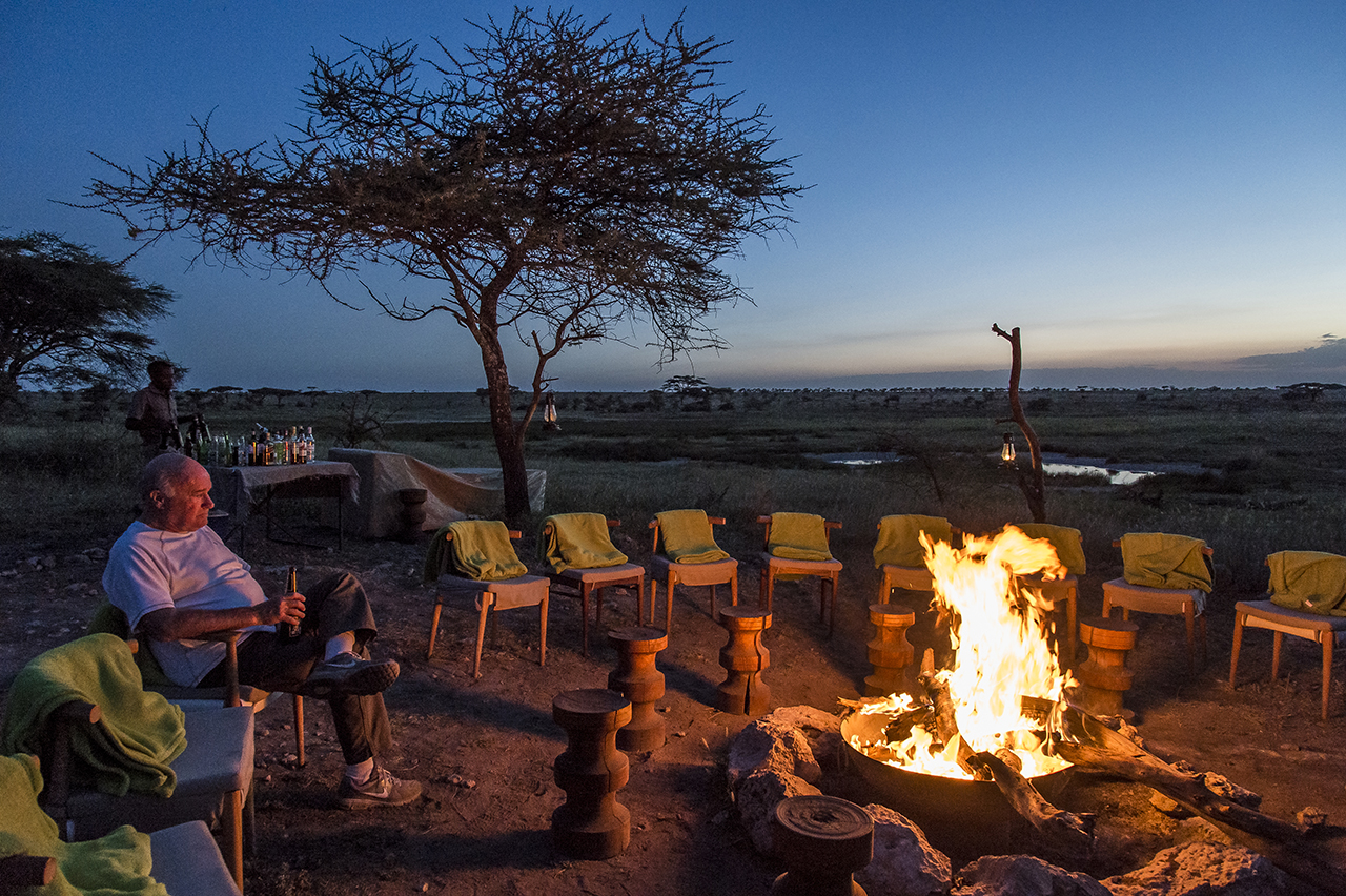 A tourist enjoys beer, next to a campfire at Asilia Camp, the only tent camp located in the eastern prairies of the central part of the Serengeti, magnet for cheetahs and lion, out of the frequent passing paths of tourists , because out of the way. The permanent camp of 8 luxury tents is set up more than an hour from its nearest neighbor. Approximately 2,700 beds in approximately 120 safari camps are available throughout the park.