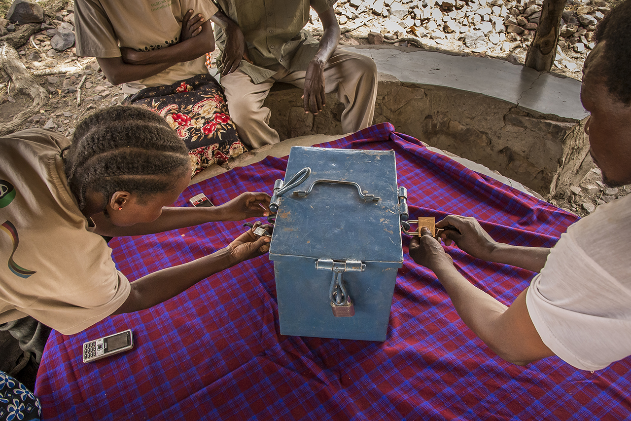 """Village of Nyichoka, about 30 kilometers west of the Serengeti, the members of the group """"Sinduka Cocoba"""" gather around a table on which is placed a blue metal box closed by three padlocks After an immutable ritual, the box is unlocked. Four plastic boxes filled with banknotes are stored there. They contain the total assets of the local """"Conservation Bank of Nature"""". Each member pays """"shares"""" of 4,000 Tanzanian shillings (about two euros).  Members meet every Saturday around this micro-credit project. Debts are then repaid and disbursements made. Members invest in projects that guarantee their livelihood. The only condition of the loan: that nature is not affected by the funded project."""