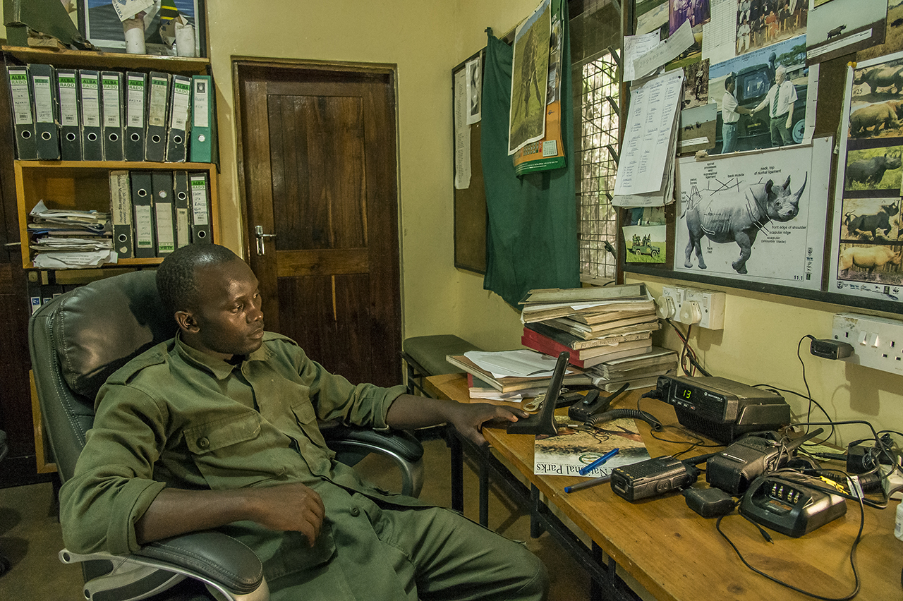 """TANAPA (Tanzania National Parks) rangers' guard station in Moru, southern Seregenti. Ngoti, chief of rangers on standby in the radio room. 52 rangers control an area of ,000 square kilometers to protect the last 30 black rhinoceros in the south of the Serengeti. The rest of the park is home to 20 other animals. Each of them is a treasure, for to the poachers nothing is as precious as their horn. """"If a poacher can choose between killing a group of elephants or a rhinoceros, he will kill the rhino,"""" Ngoti said. """"The price on the black market for the horn, the material of which is similar to that of the nails, is in Vietnam or China at more than $ 10,000 per kilo"""".  Ngoti and his men can be proud of their work. By the early 1990s, poachers had reduced the Serengeti's rhinoceros population to only two females, until the moment when, from the nearby protected area of gorongoro, Rajabou, a male, migrated. A stroke of luck. Thus, while slaughtering animals in South Africa results in degeneration, the Serengeti population is growing. Currently, five to six pups are born each year."""