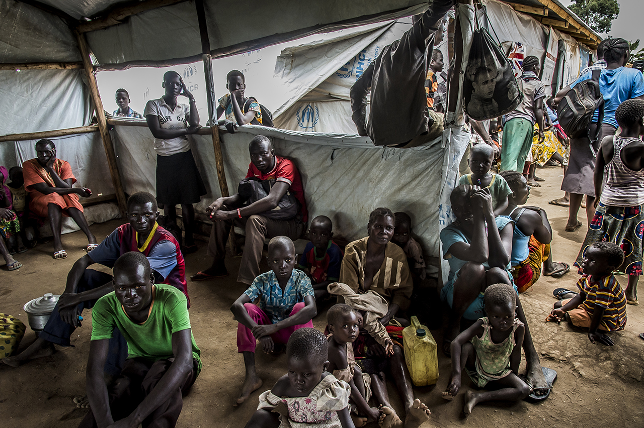 In a transit camp, refugees wait before being called to be transported to Imvepi's main reception center, a two-hour drive away. They were taken in charge from next to the border between South Sudan and Uganda. From different points of entry, refugees are gathered in small transit camps, such as this one, where they are offered food, water and where they are quickly treated.