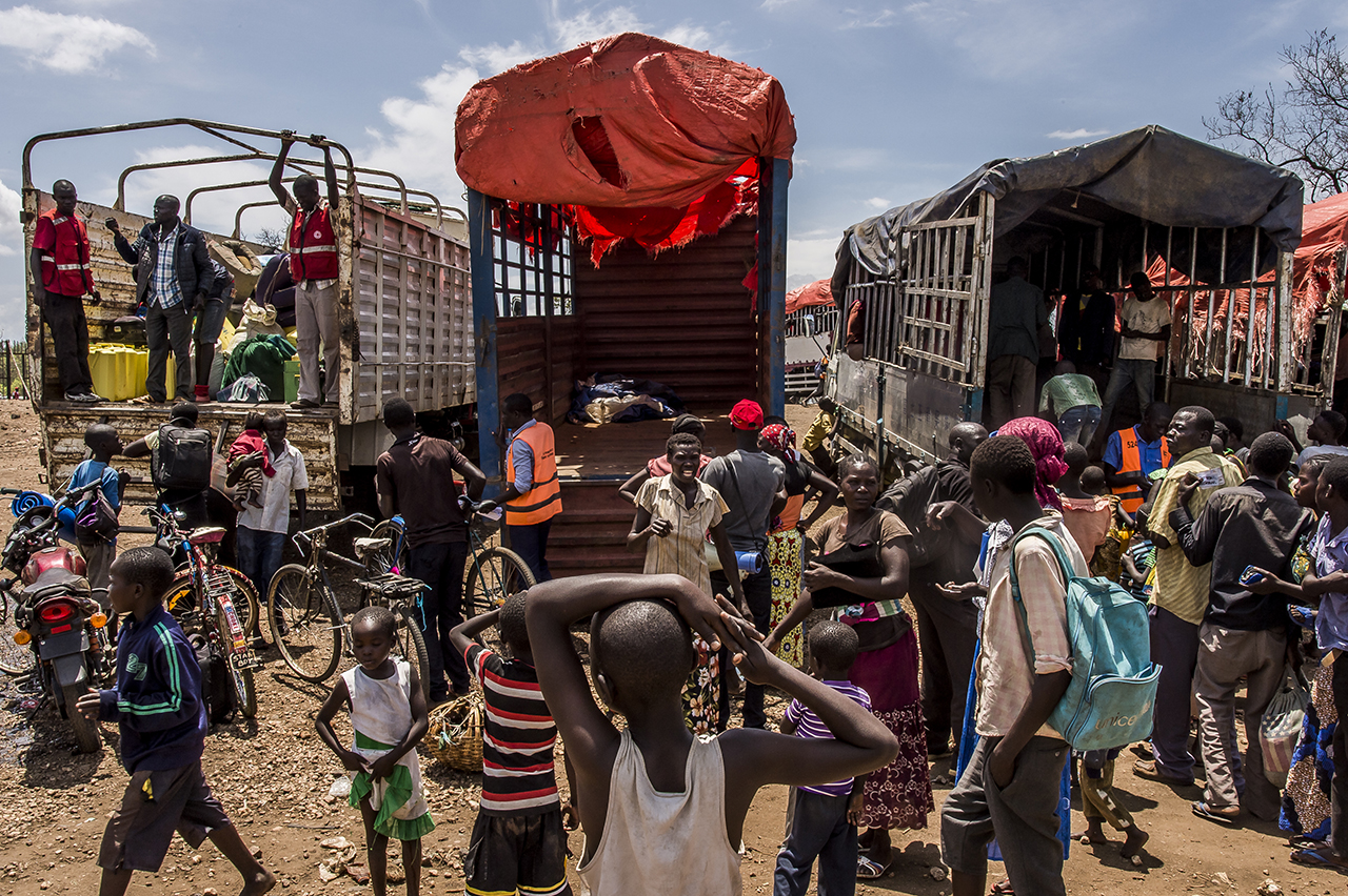 Imvepi reception center - Refugee families board on trucks that will drop them with their belongings at spots in the Bidibidi camp, where an official from the Prime Minister's Office will allocate a piece of land for them to settle.
