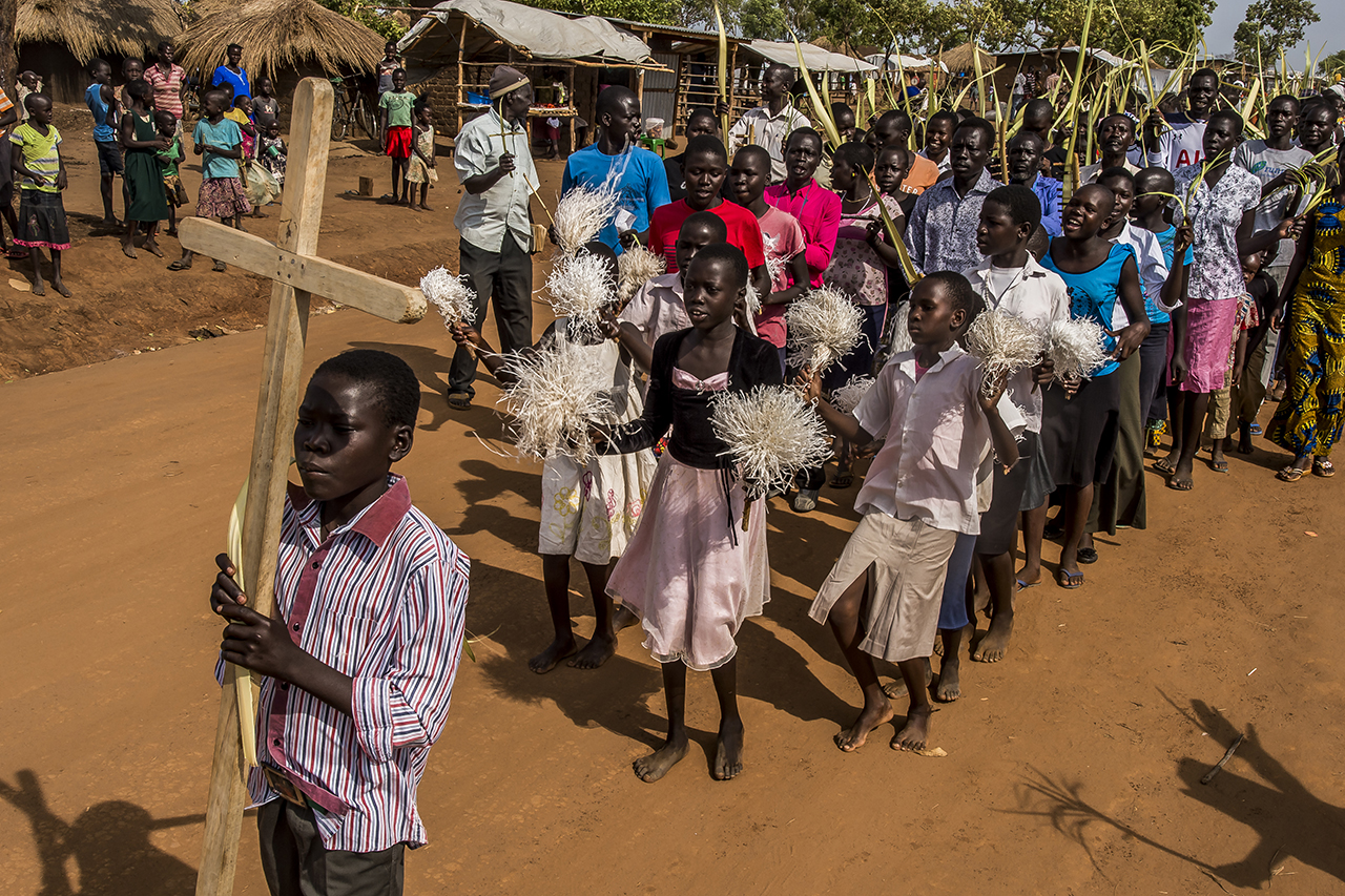 On Palm Sunday, a procession walks through some areas of the Bidibidi settlement area. It will end under a large tent that serves as a church to the many South Sudanese Catholics, durant a service with the delicate sound of traditional harps.