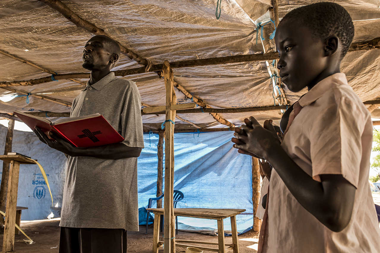 In the settlement area of Bidibidi, a Catholic religious service in the Church, a large tent. That day, the service began with the procession of palms. Father Lutor Francis, 58, officiates. The only things he could bring back from South Sudan are his Bible and his red prayer book.
