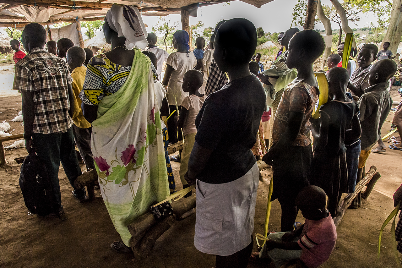 On Palm Sunday, after a procession through areas of the Bidibidi settlement area, a religious service is held under a large tent that serves as a church for many South Sudanese Catholics.