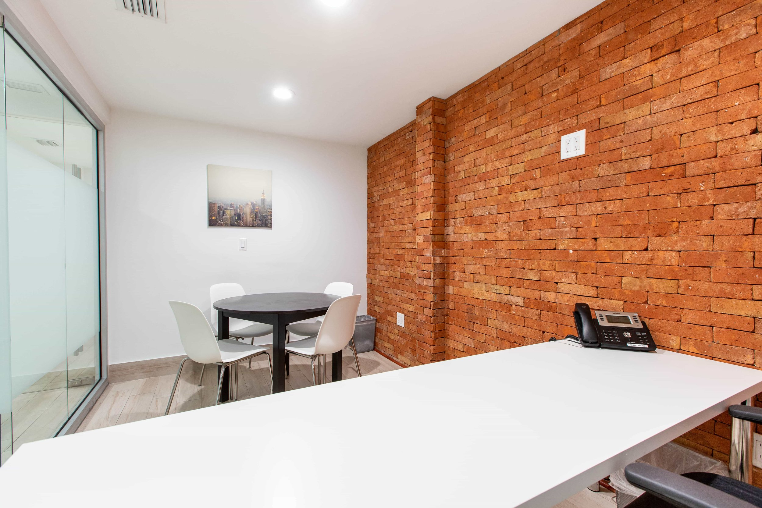Medium size office with small conference table.