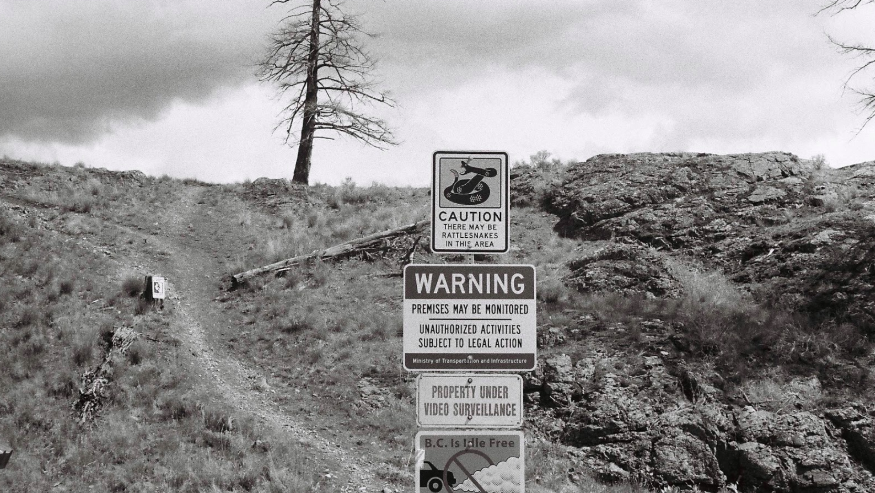 Warnings posted in the Okanagan: rattlesnakes, trespassing, surveillance, exhaust. 2017.