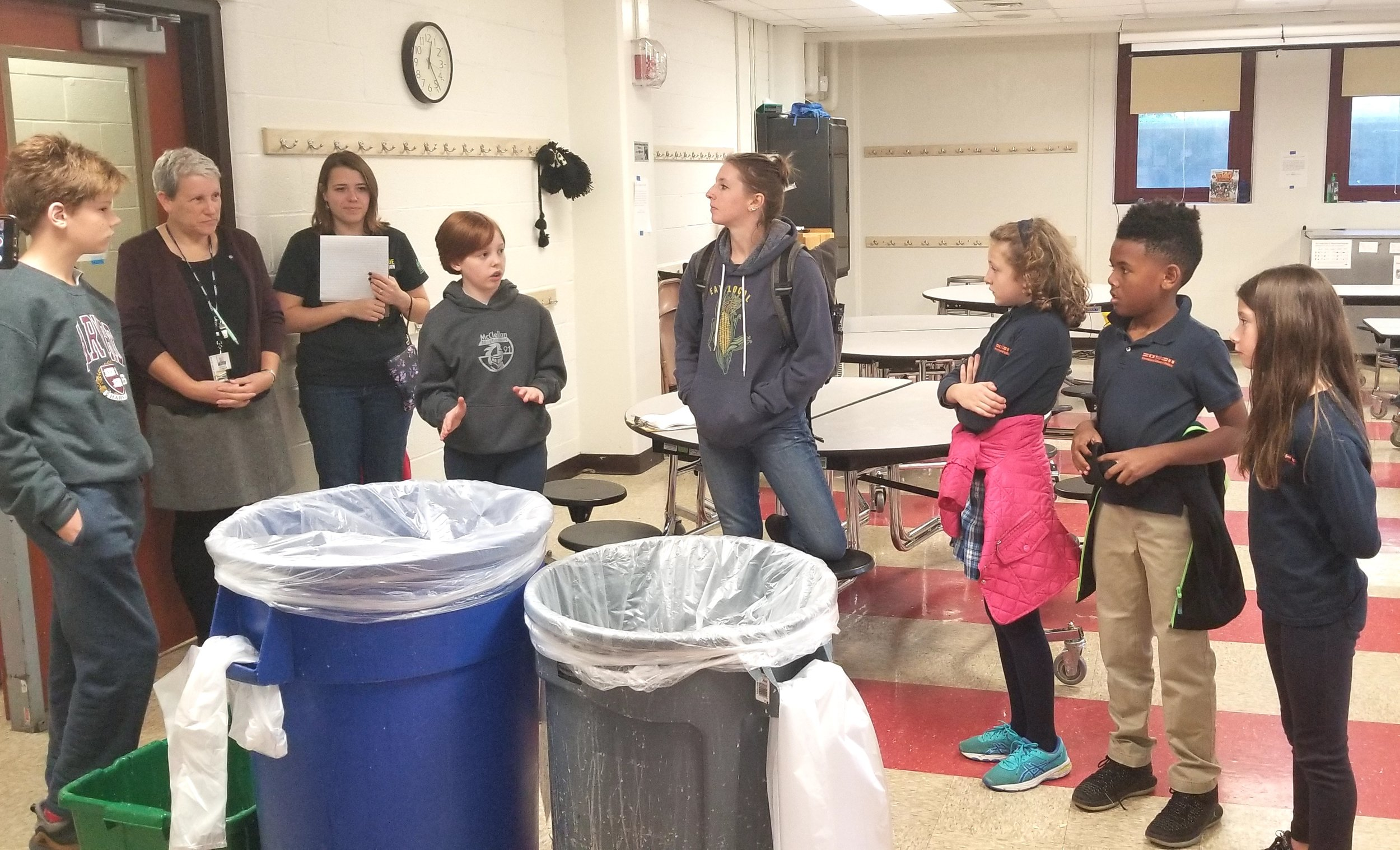 Ella, fourth from left, explains the Zero Waste Cafeteria stations to three International School Students.