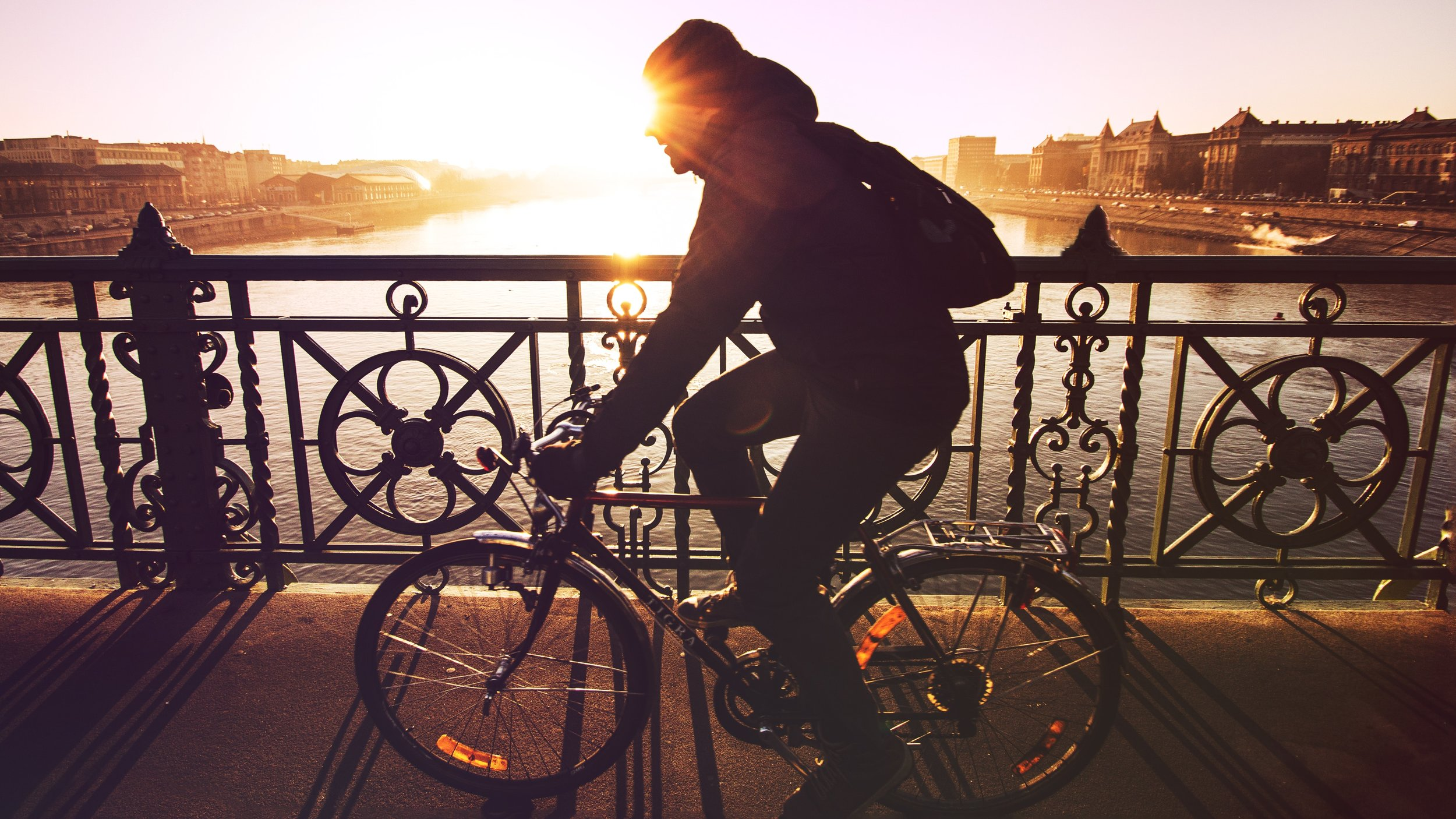 A man cycling across an urban bridge