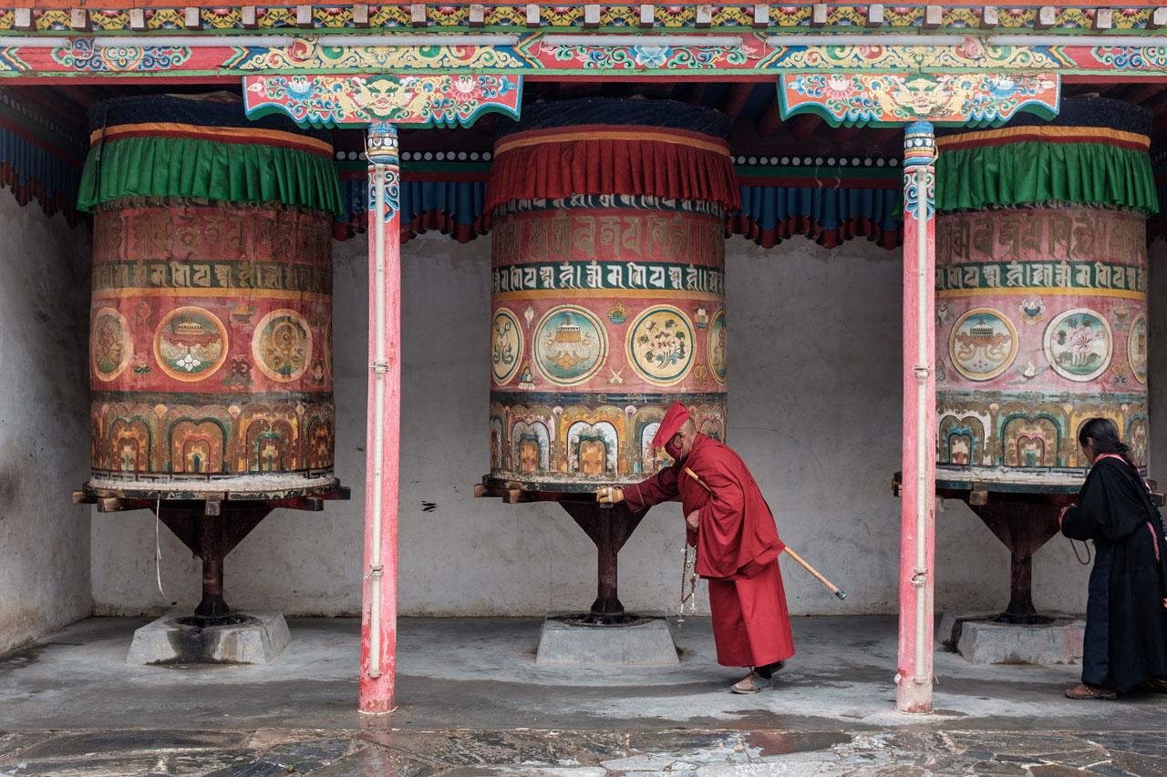 tibetan monk spinning prayer wheel in yushu city