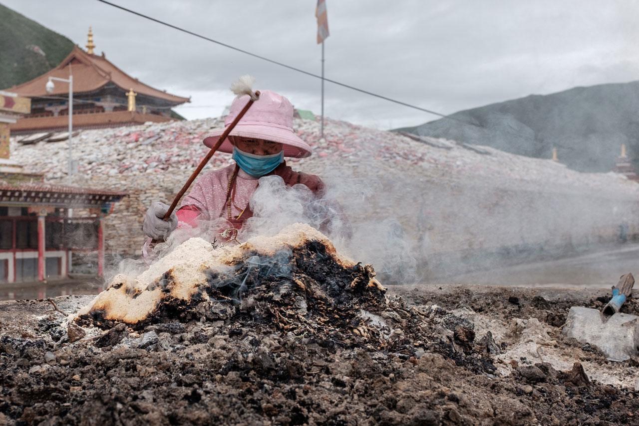 tibetan woman performing ritual in yushu city