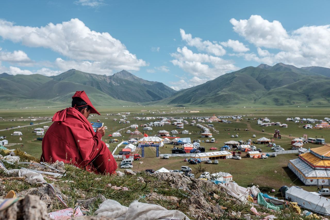 young tibetan monk sitting on hill and reading
