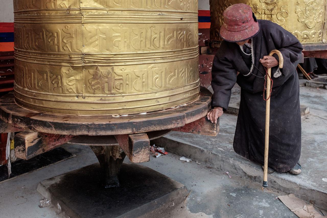 old tibetan woman spinning golden prayer wheel