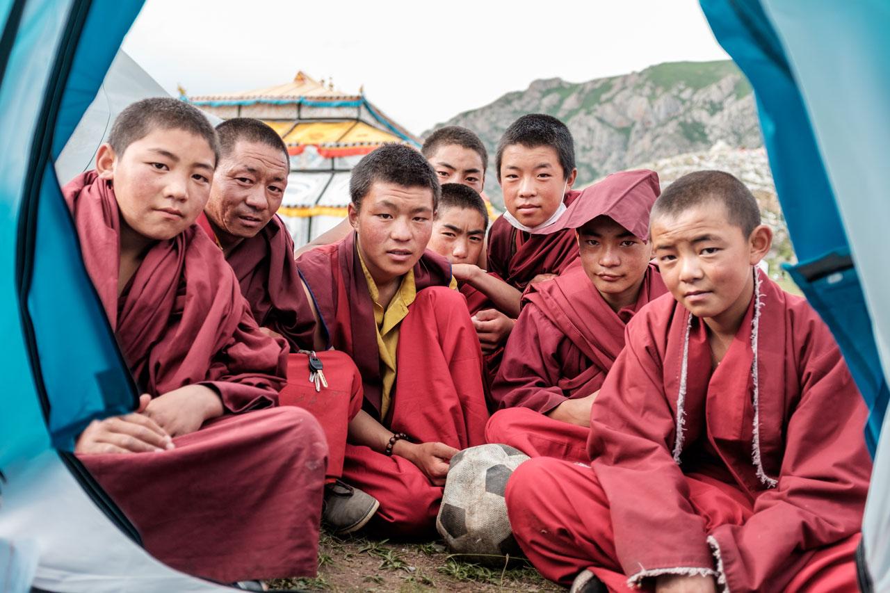 tibetan monks sitting in front of tent