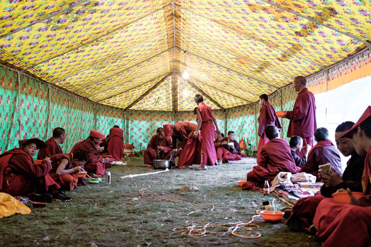 tibetan monks having dinner in their community tent