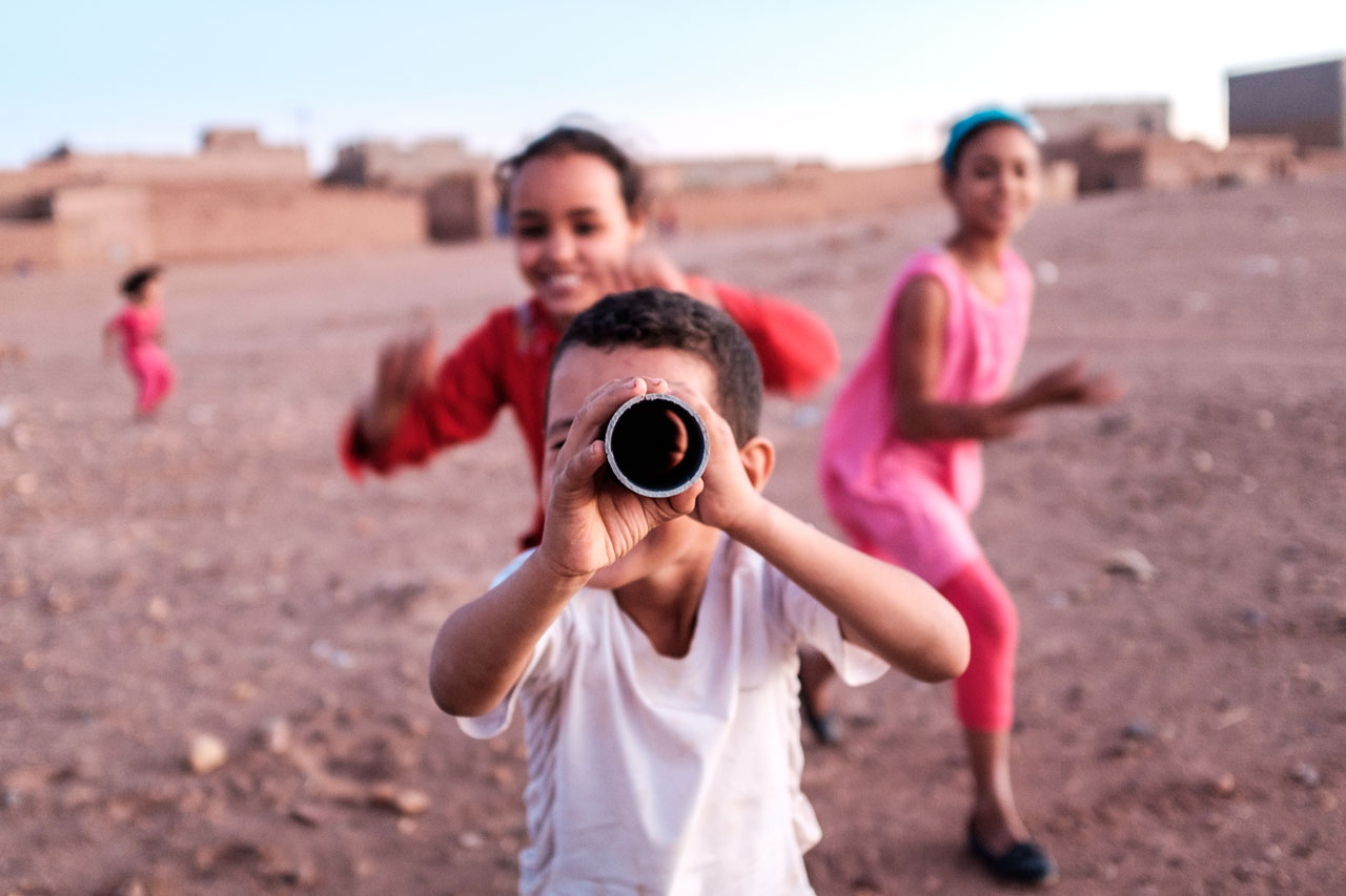 morocco desert village kid imitating photographer