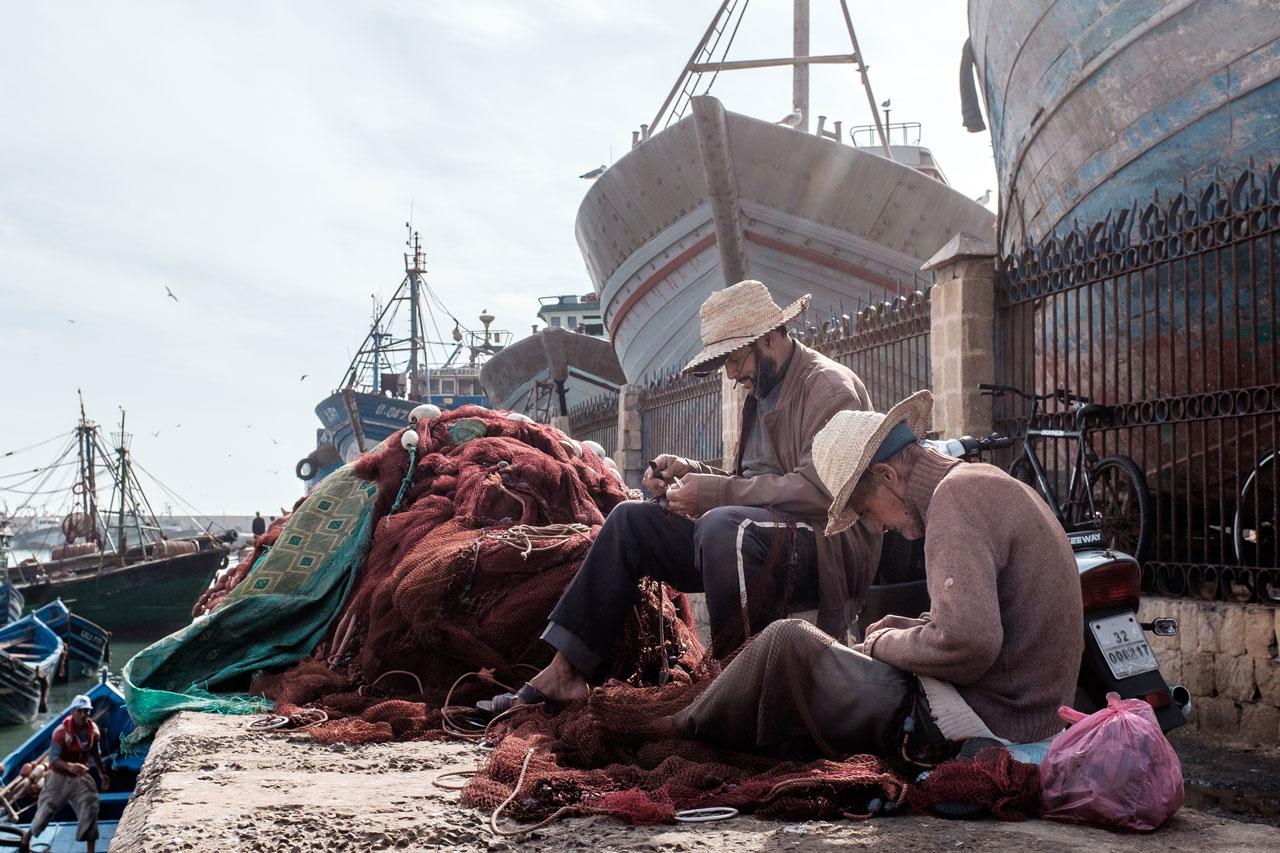 morocco essaouira fishermen repairing net