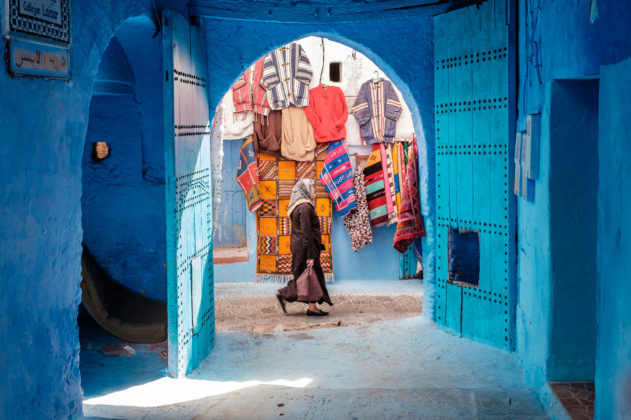 morocco chefchaouen woman walking in blue alley