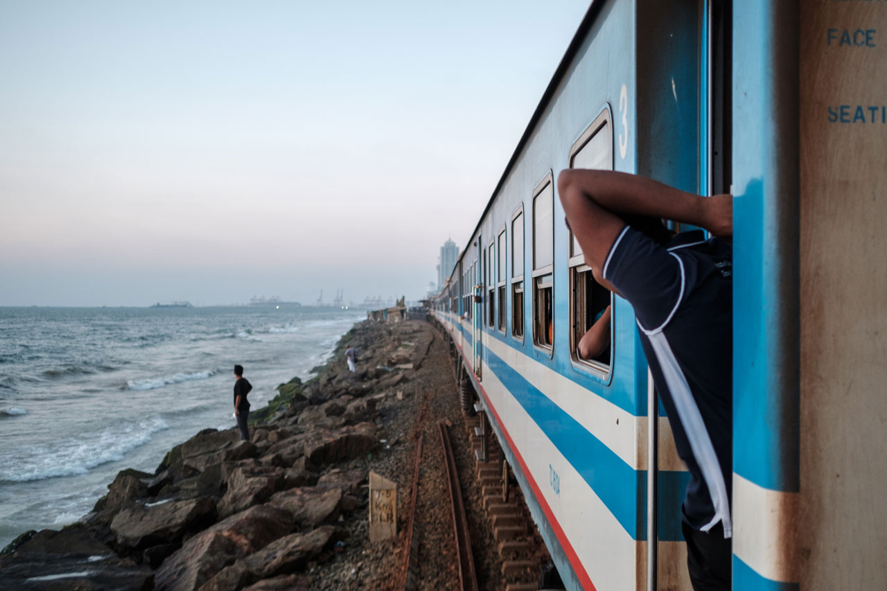 Copy of man leaning out of train next to ocean colombo sri lanka