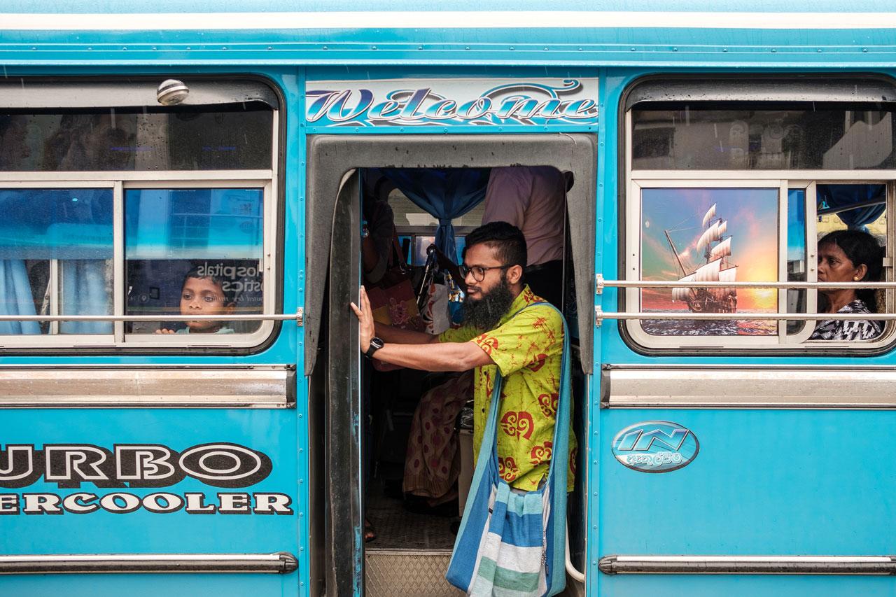 Copy of man in yellow shirt standing in bus door kandy sri lanka