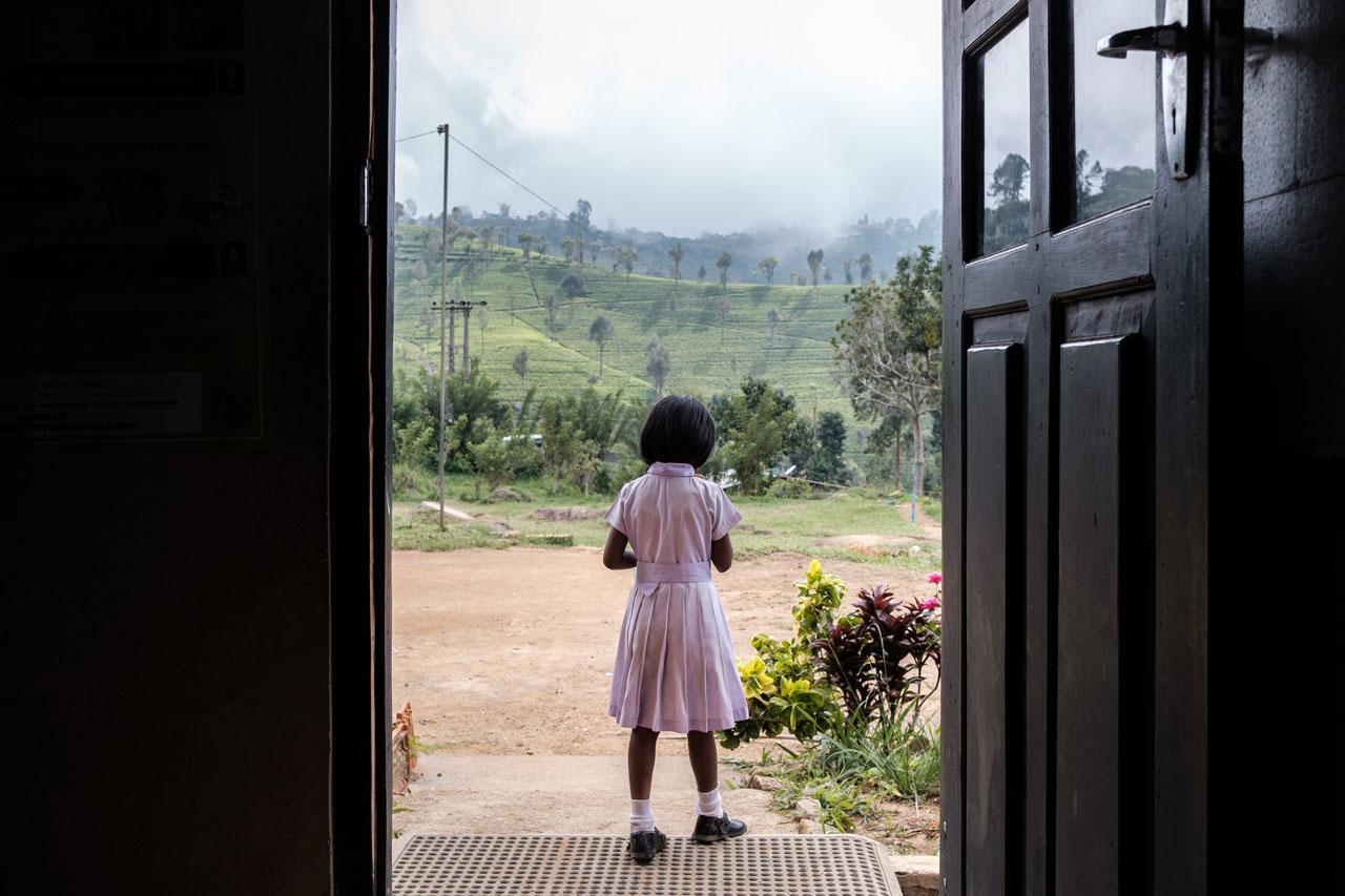 Copy of school girl in front of door looking at hills sri lanka