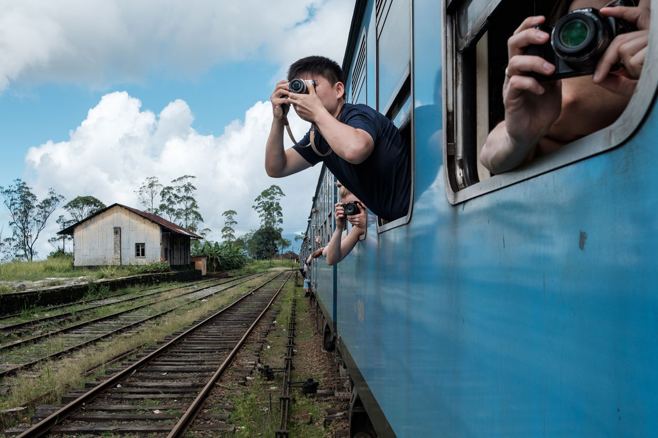 Copy of tourists taking pictures of tea plantages out of train sri lanka