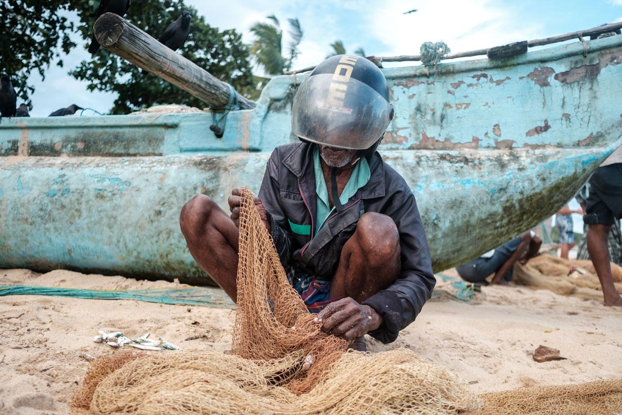 Copy of fisherman in helmet inspecting fisher net in tangalle sri lanka