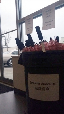 """The sign above reads """"Umbrellas for the smokers. Please return after use"""""""
