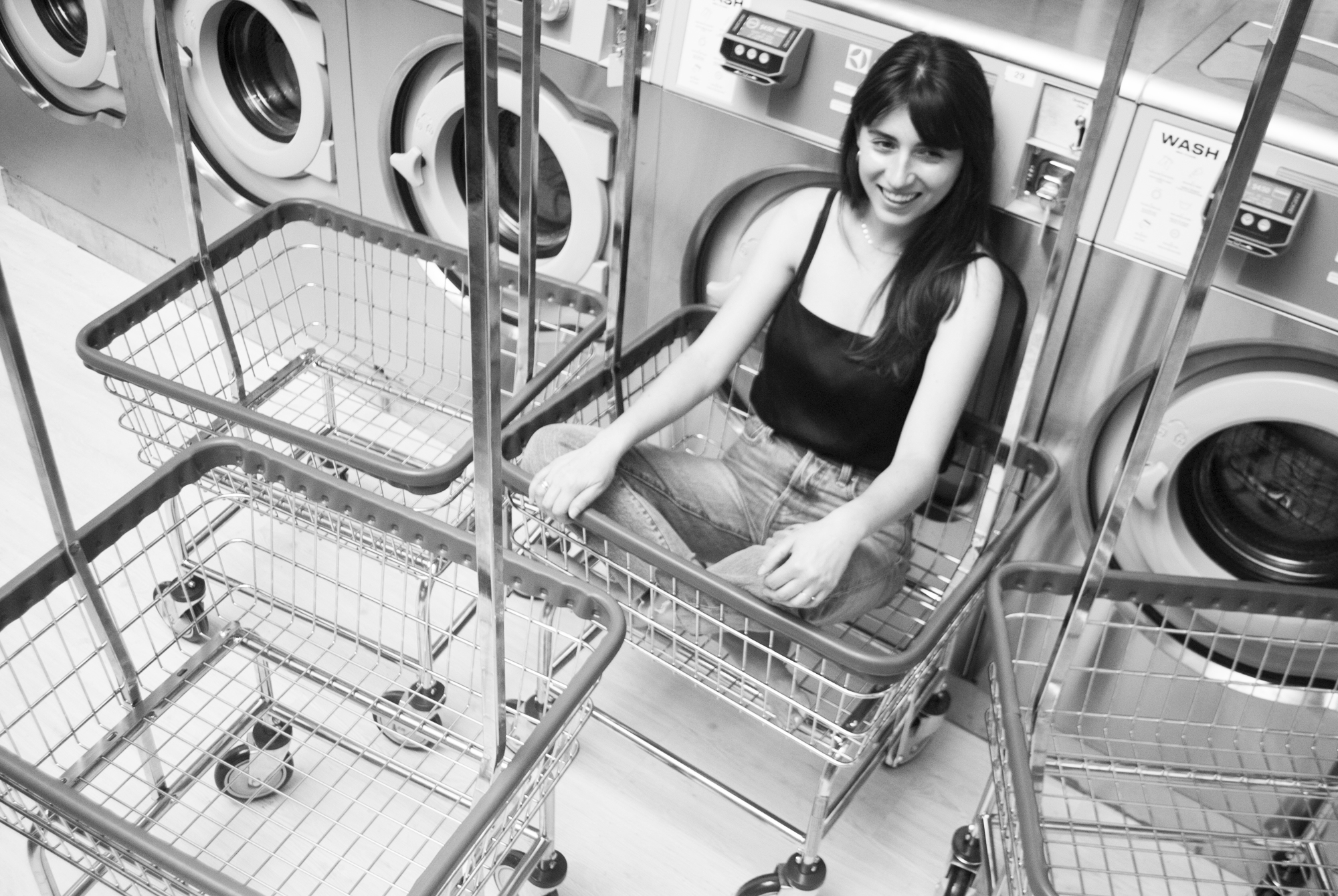 Ariana sitting peachy keen in her laundry dolly.