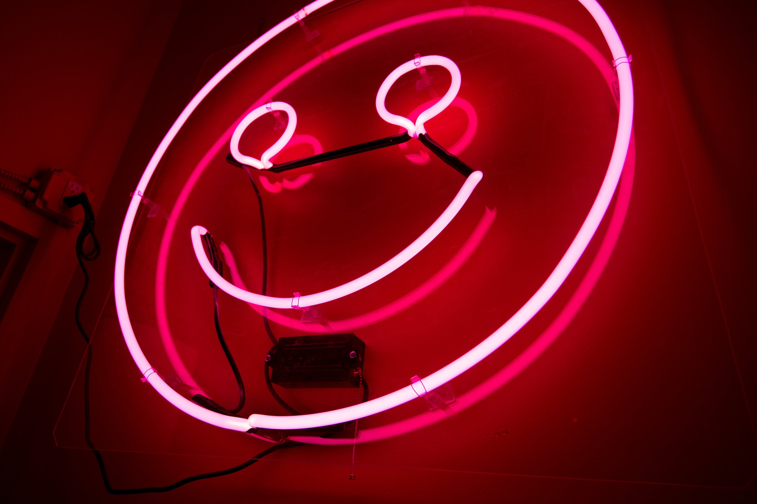 The neon happy sign in the stairwell of the Color Factory.