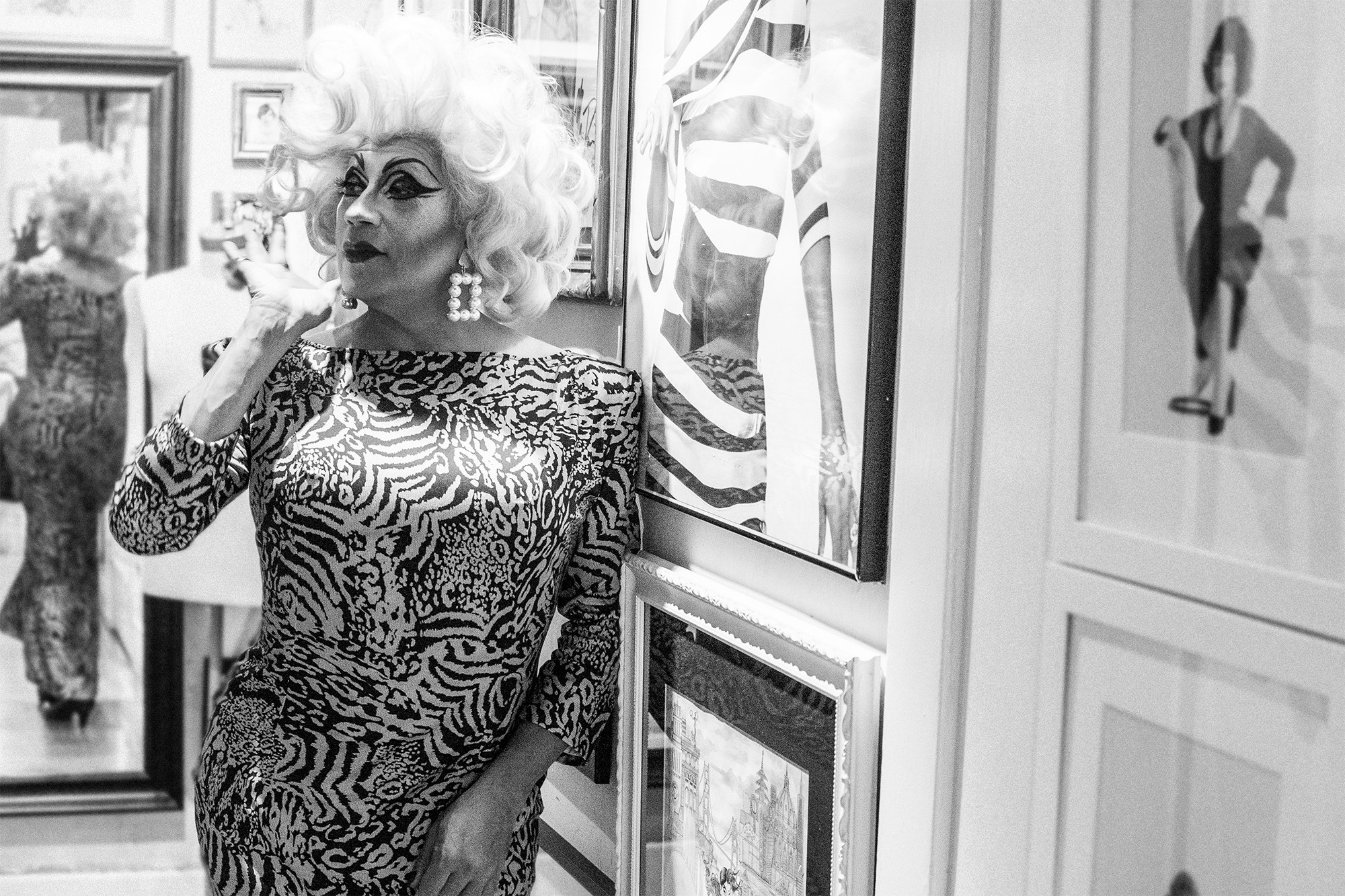 Juanita More! in her Nob Hill apartment, effortlessly being chic amongst the artist rendering of her many years in the drag and queer scene.