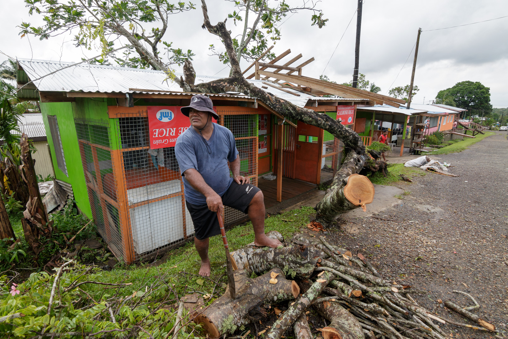 A shopkeeper chops up a tree that had fallen on his roof during Cyclone Winston, as a cleanup continues in the aftermath of the storm in Fiji's capital Suva, February 22, 2016.