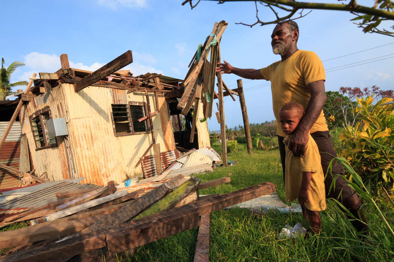 Ikavatu from the village of Namena in Tailevu, Fiji, gestures towards his damaged house after Cyclone Winston swept through the area on February 20, 2016.