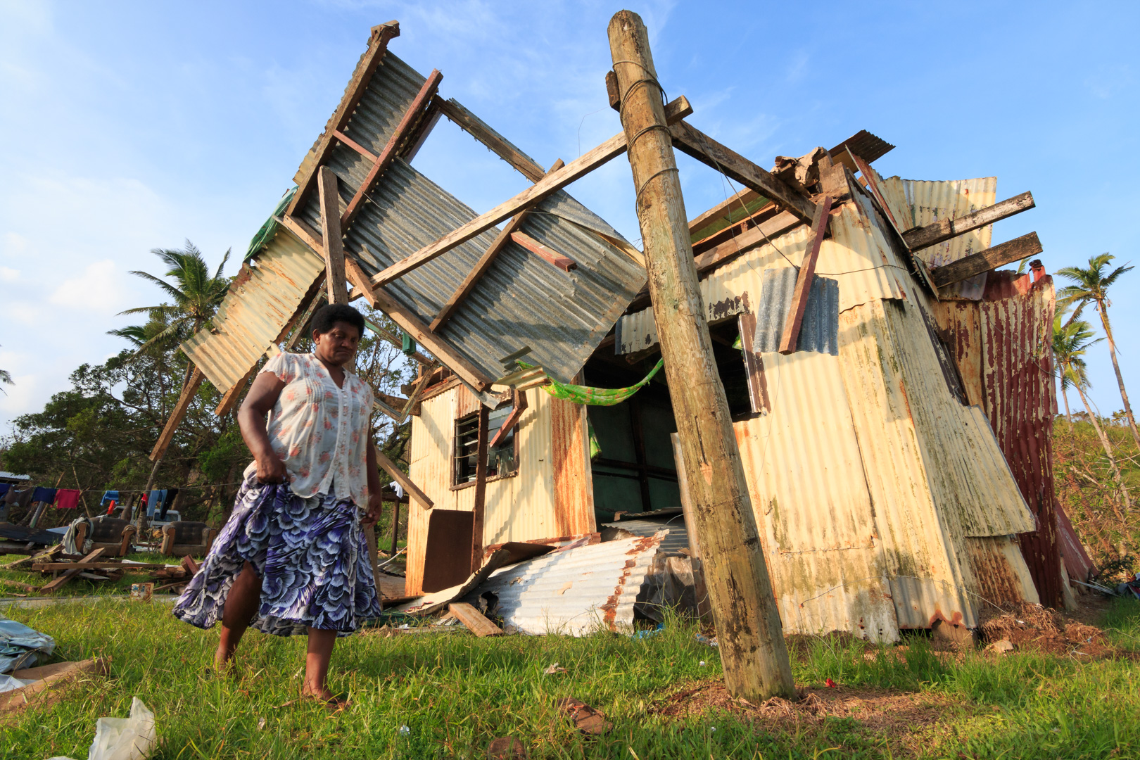 A woman from the village of Namena in Tailevu, Fiji, walks in front of her damaged house after Cyclone Winston swept through the area on February 20, 2016.
