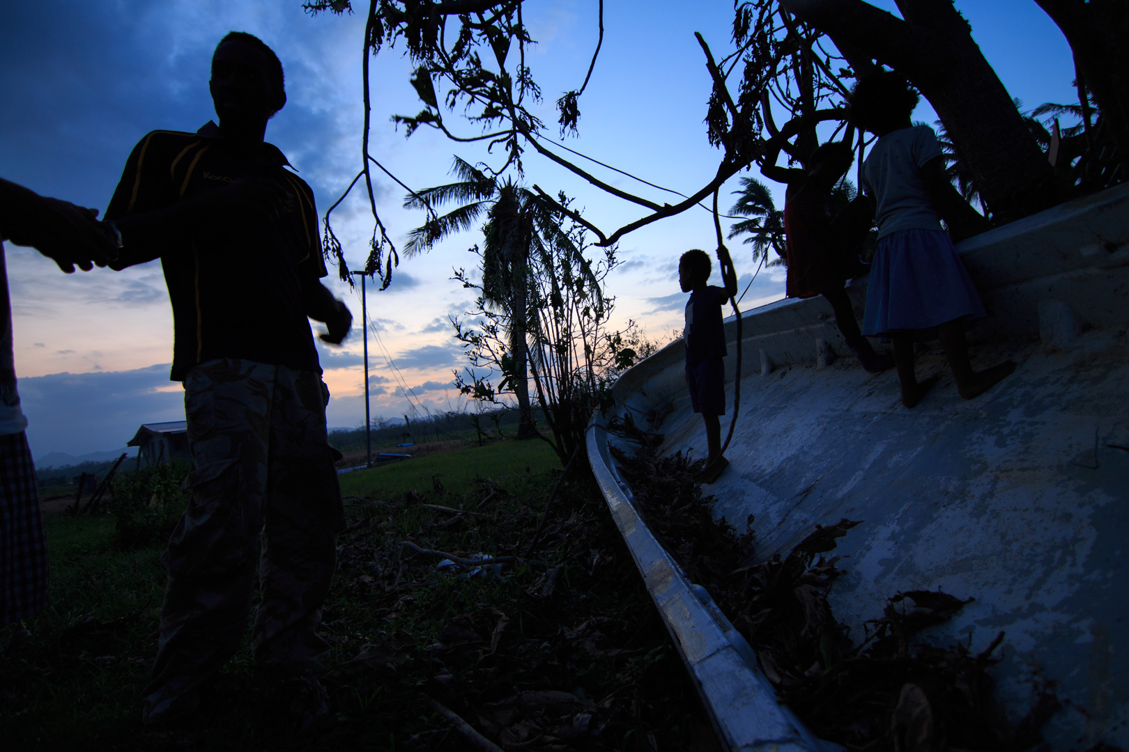 A man from Drau-ni-ivi Village in Rakiraki gestures as children play in the hull of an overturned boat behind him after Cyclone Winston swept through the area and made landfall in Fiji on February 20, 2016.