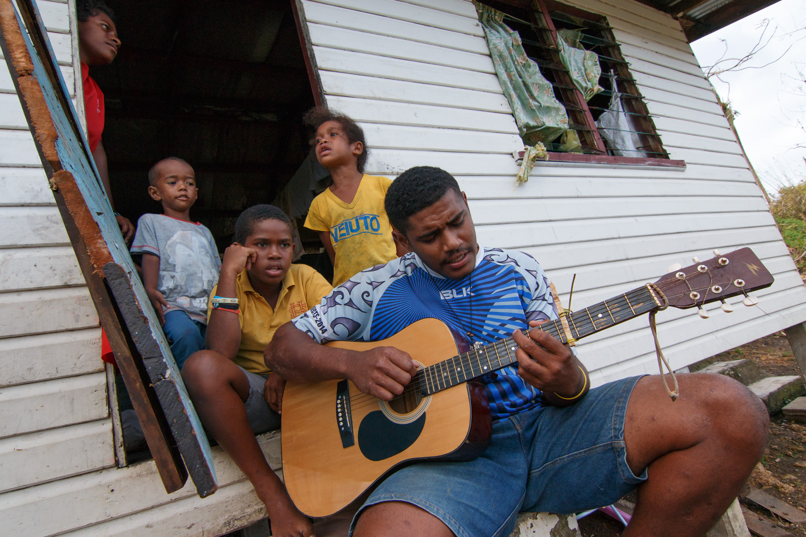 Children play guitar and sing songs to pass time while cleanup is underway in Naiseralagi village in Rakiraki, Fiji, after Cyclone Winston swept through the area on February 20, 2016.
