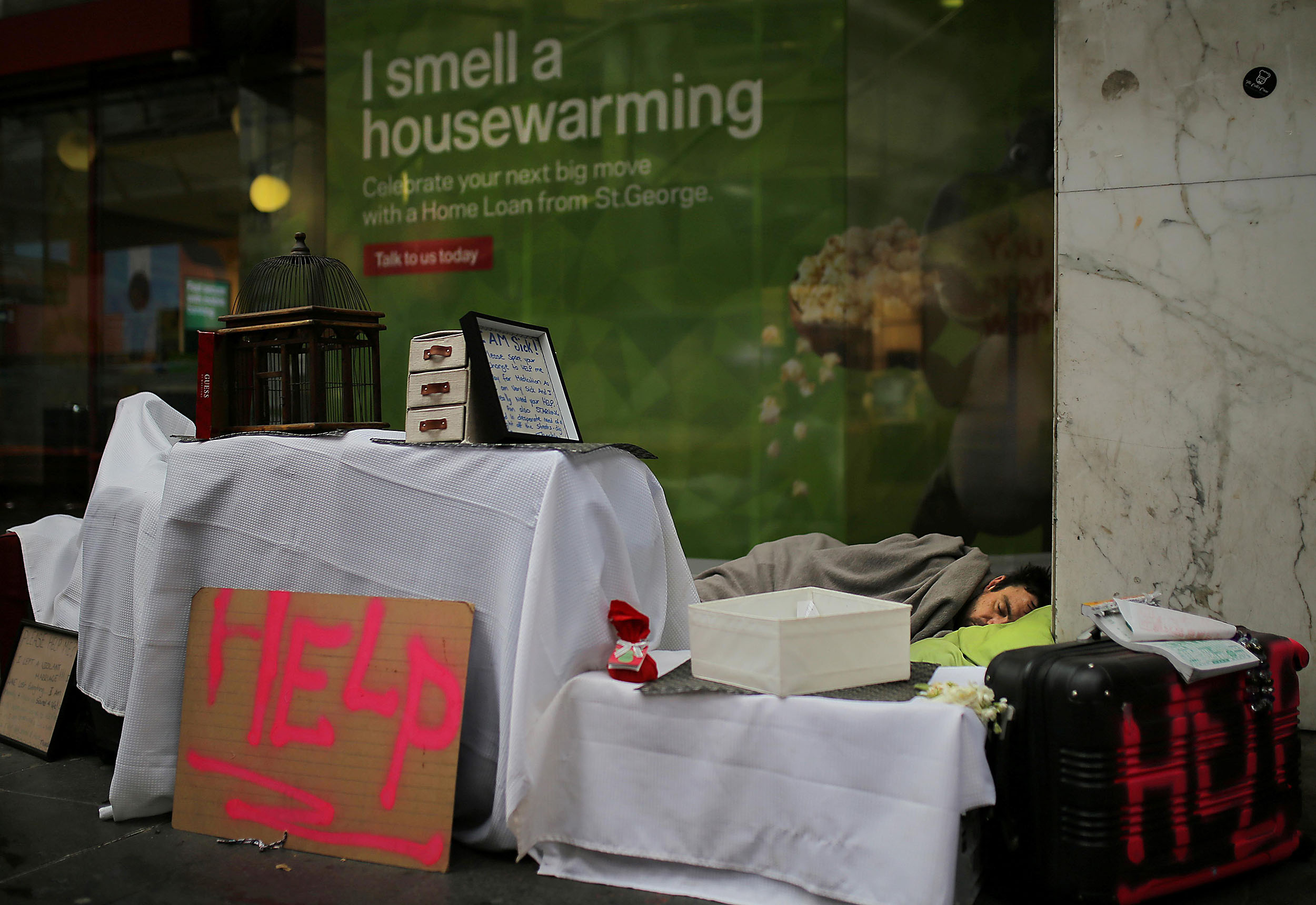 A homeless man sleeps in a makeshift encampment in front of a bank displaying a home loan advertisement in central Sydney, Australia, July 31, 2017.