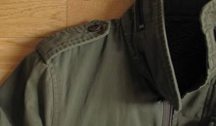 Epaulettes déboutonnables et capuche en nylon qui s'insère derrière la nuque
