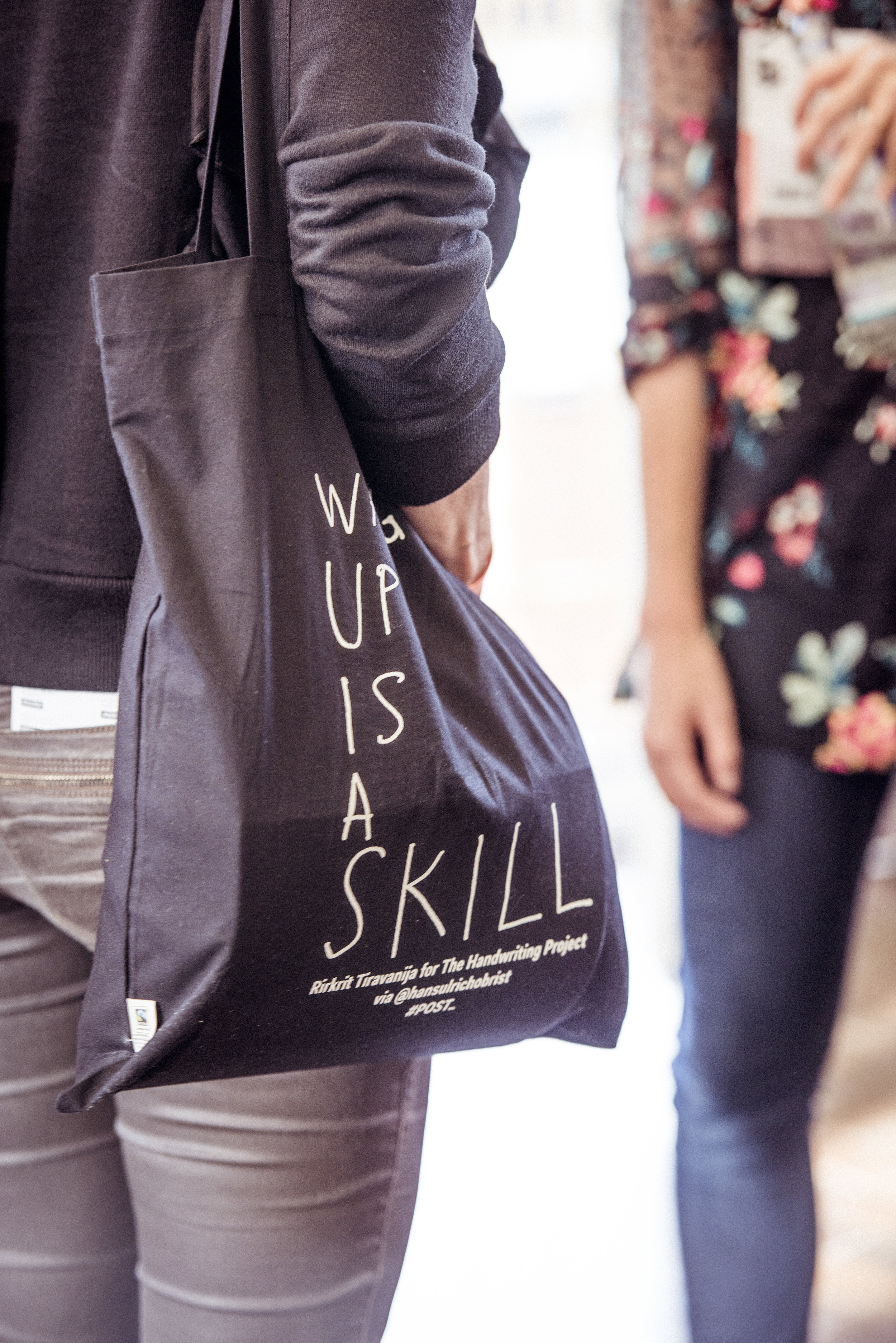 """Waking Up Is A Skill"" by artist Rirkrit Tiravanija for POST_, a project by Hans Ulrich Obrist and ForYourArt. Key phrases from POST_ were selected to be featured on guest totes, displayed on event walls, and showcased on screen between sessions (photo by Stefanos Notopoulos)."
