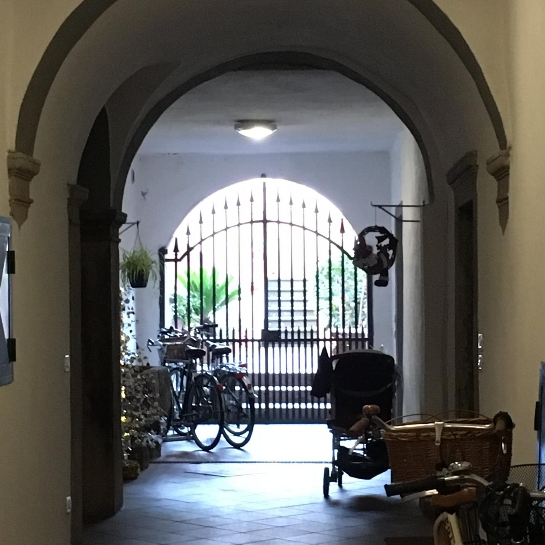 Entry to apartment on Via Pelleria, just inside the front door, with a pretty private garden beyond the gates.